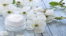 Un pot de crème hydratante maison avec des fleurs blanches à côté