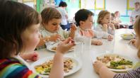 Différents enfants mangeant à la table d'une cantine scolaire
