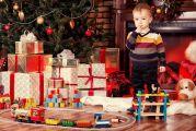 enfant regardant un mont de cadeaux de noël au pied du sapin