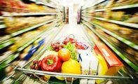 Caddie chargé de nourriture traversant une allée de supermarché