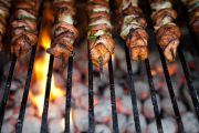 Alignement de cinq brochettes de viandes en train de cuire sur une grille de barbecue