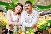 Couple accoudé sur un caddie entre les étals de fruits et légumes