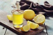 Flacon rempli d'une préparation à base de citron posée sur une table à côté de citrons coupés