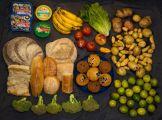 fruits légumes pains et gâteaux étalés sur une nappe noire