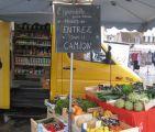 Camionnette jaune de l'épicerie itinérant l'Hirondelle et cagettes de fruits et légumes exposées