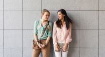 Deux femmes habillées mode se regardent et sourient