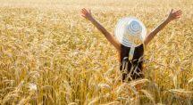 Femme écartant les bras dans un champ