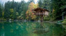 Une maison surplombe un lac, perchée dans les arbres. Son image se reflète sur l'eau.