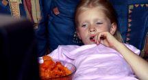 jeune fille mangeant un saladier de chips devant la télévision