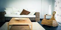 Intérieur d'un salon avec canapé, tapis table basse et fauteuil en rotin