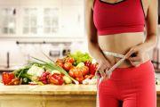une femme mesurant son ventre avec un mètre dans sa cuisine