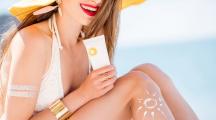 Une femme souriante positionnée de dos s'est dessiné un soleil avec une crème