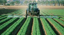 Un tracteur verse des pesticides dans un champ