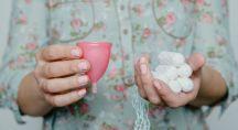 une femme tenant dans sa main droite une coupe menstruelle et dans la main gauche des tampons jetables