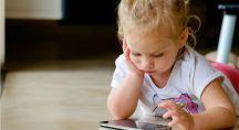 une petite fille joue sur un smartphone
