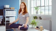 une femme zen médite sur son bureau de travail