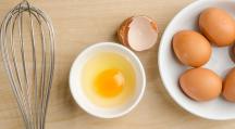 un œuf dans un bol à côté d'un fouet en cuisine