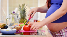 une femme enceinte fait la cuisine