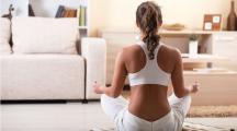 une femme pratique la méditation chez elle