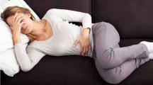 une femme allongée sur le canapé a des règles douloureuses