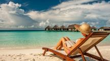 femme sur un transat qui lit un livre à la plage