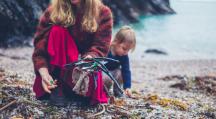 Une mère qui ramasse des déchets en bord de mer