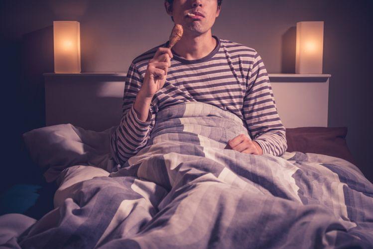 Homme mangeant un pilon de poulet dans son lit