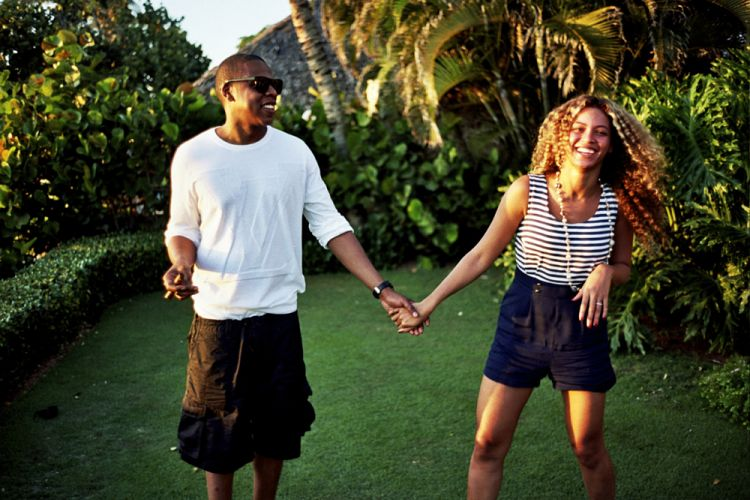 Le rappeur Jay-Z et sa femme Beyoncé se tenant la main dans un jardin tropical.