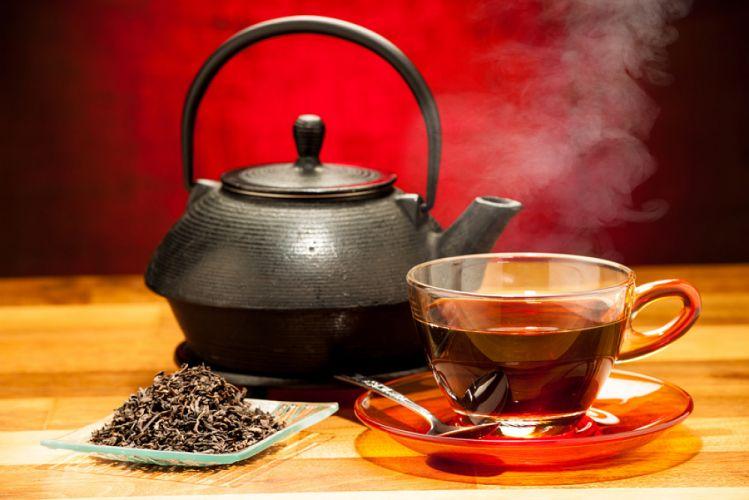 Théière chinoise, posée sur une table à côté d'une tasse de thé fumante et de feuilles de thé séchées