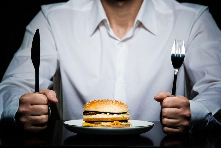 Homme tenant ses couverts devant un hamburger