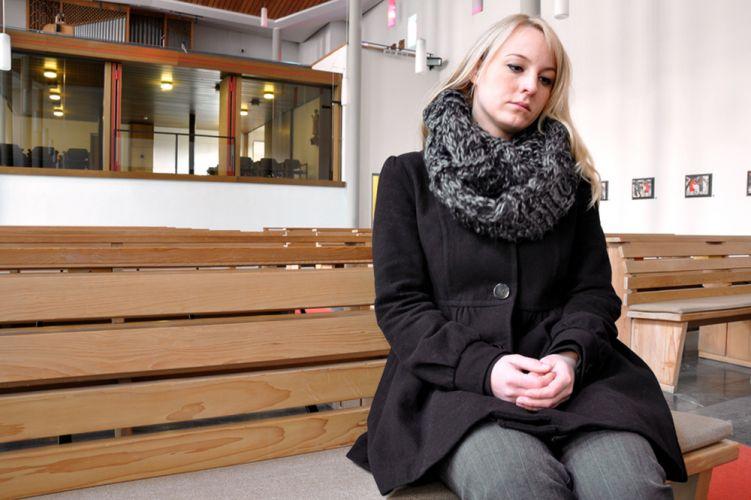 Femme avec écharpe assis sur un banc
