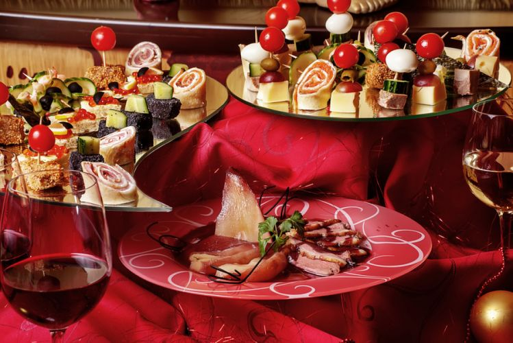 Table de réveillon comportant trois plateaux d'amuse-bouches et un verre de vin rouge