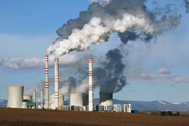 Fumée s'échappant de cheminées d'usine placée à côté d'une terre