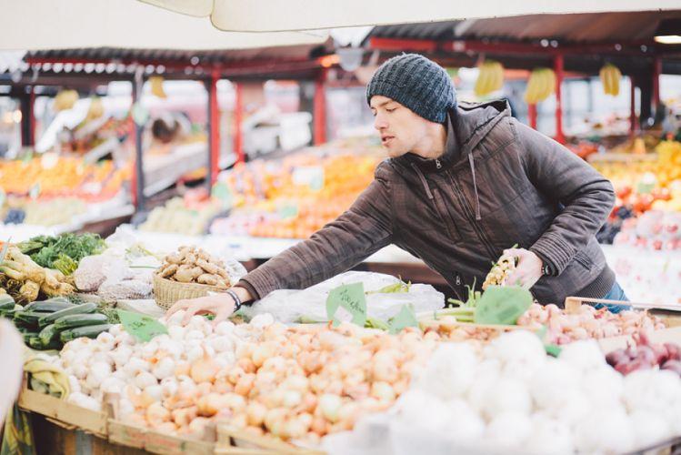 Maraîcher vendant ses légumes derrière son étal