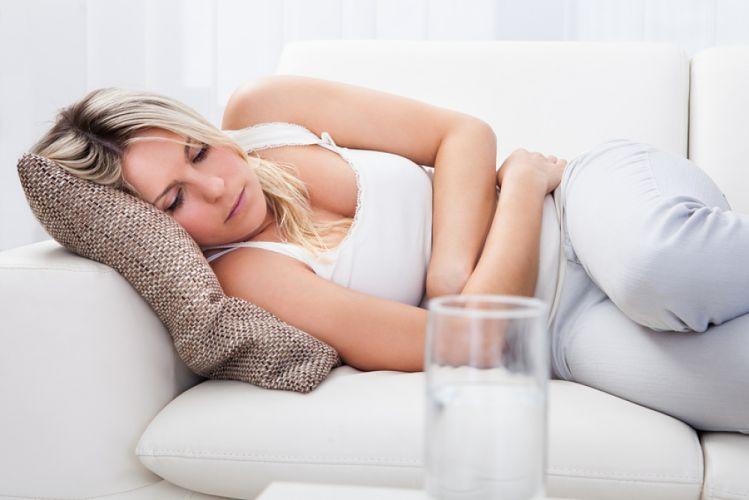Femme allongée sur son canapé et se tenant le ventre