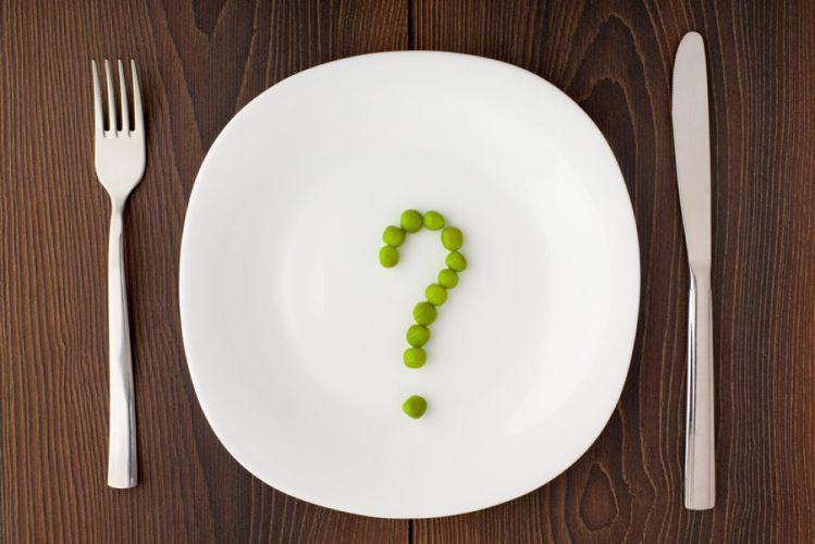 Assiette blanche contenant un point d'interrogation fait de petits pois