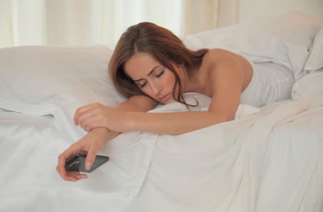 Femme endormie dans son lit tenant son téléphone à la main