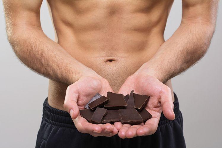 Homme musclé tenant du chocolat noir dans le creux de ses mains