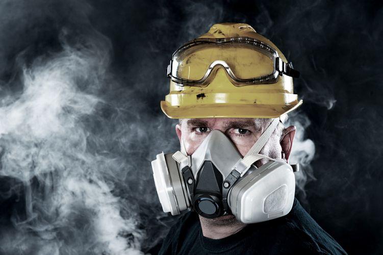 Homme portant un masque à gaz entouré de vapeurs