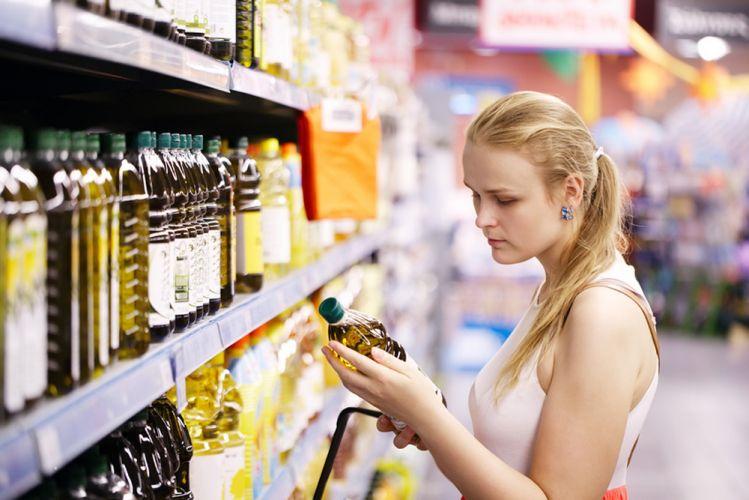 consommatrice hésitant sur une huile au magasin