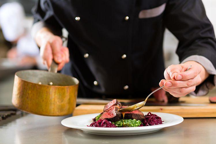 Chef cuisinier en train de dresser une assiette contenant de la viande