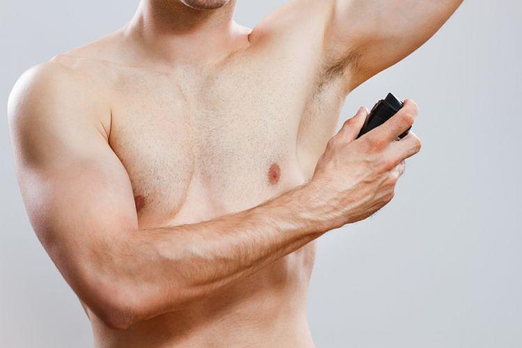 homme torse nu s'appliquant du déodorant en spray sous l'aisselle gauche