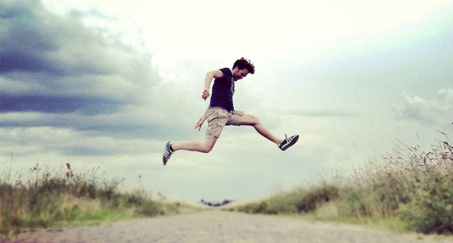 homme sautant sur une route pavée bordée d'herbes hautes