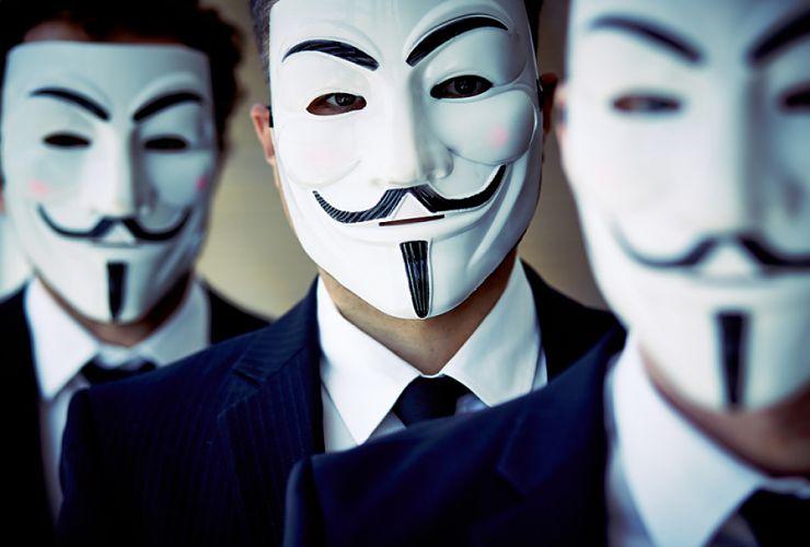 Trois hommes portant des masques anonymous
