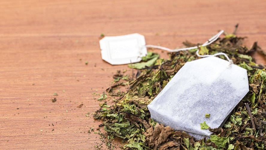 sachet de thé posé sur un petit amas de feuilles de thé séchées