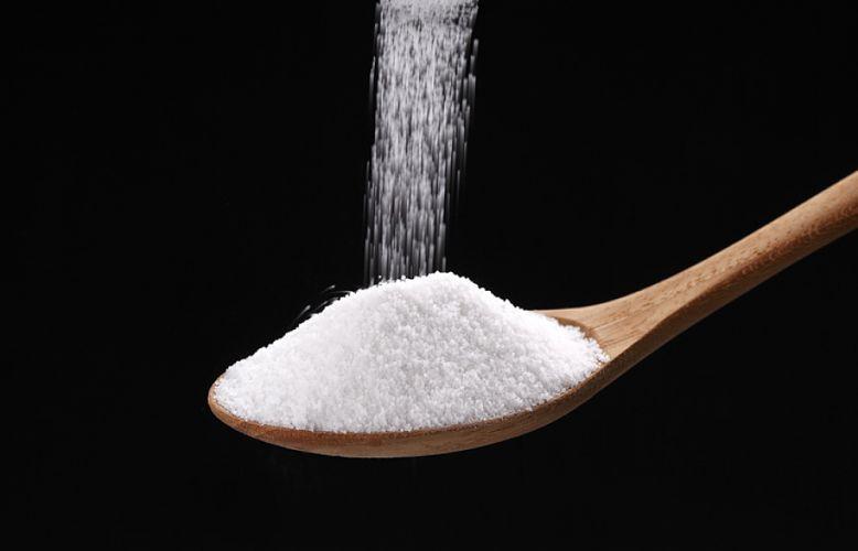sucre versé dans une cuillère en bois