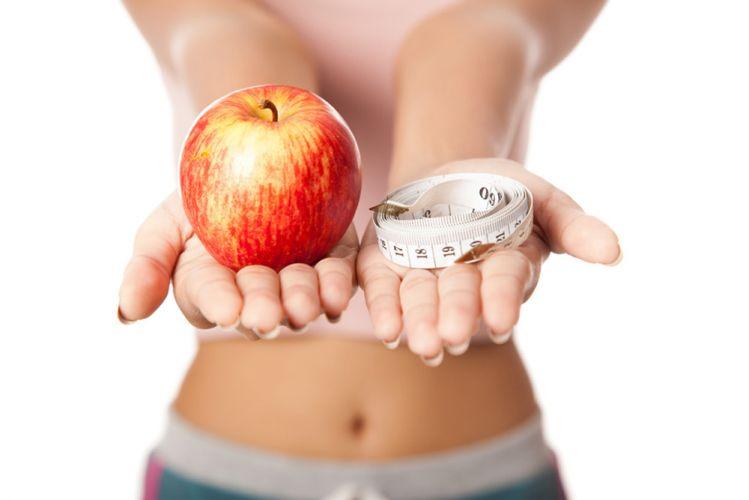 Jeune femme présentant une pomme et un mètre dans chaque main les bras tendus