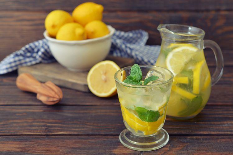 Pichet et verre de jus de citron et coupelle de citrons jaunes