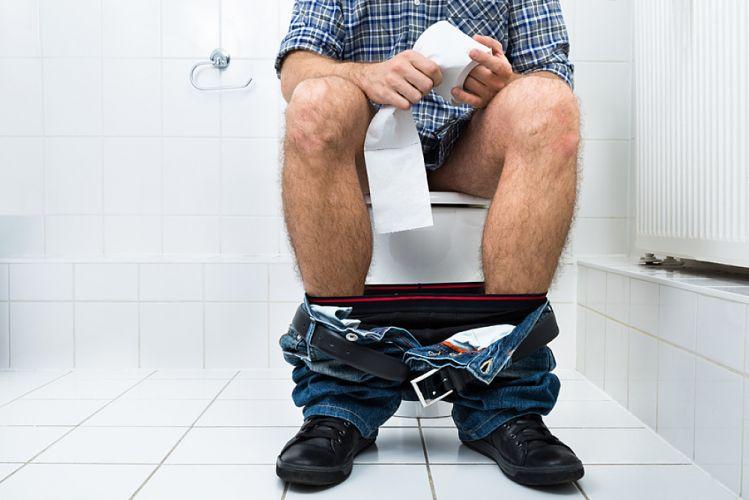 homme assis sur les toilettes tenant un rouleau de papier dans les mains
