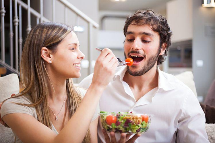 Jeune couple qui mange une salade